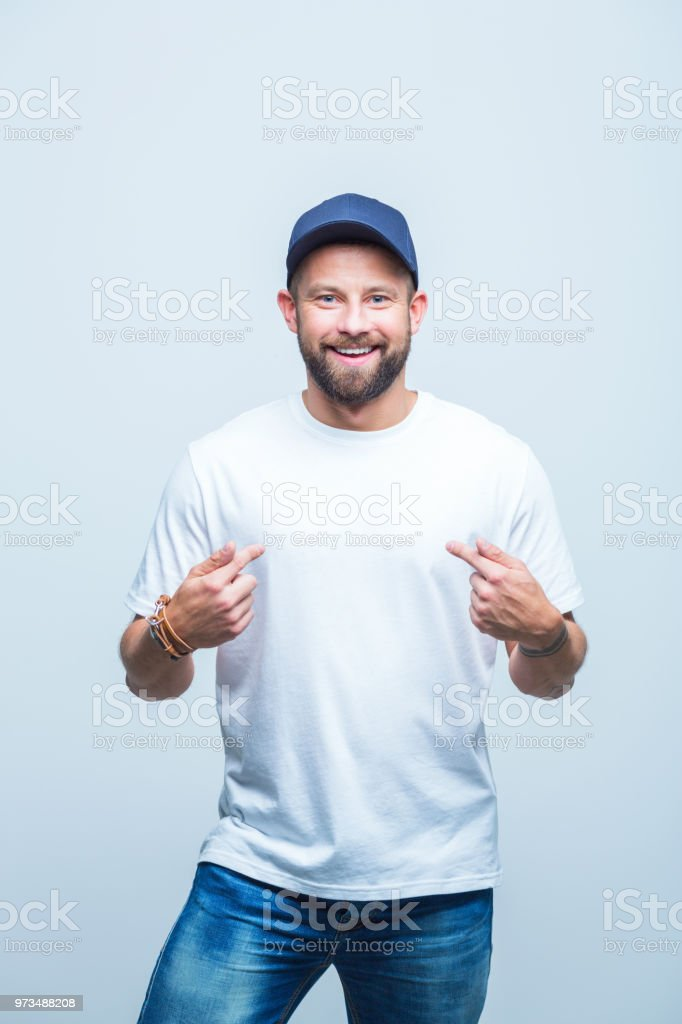 Handsome man pointing at himself Portrait of handsome young man pointing fingers at himself and smiling Adult Stock Photo