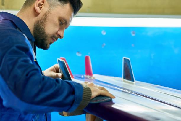 stilig man polering cistom surfing board i verkstad - surf garage bildbanksfoton och bilder