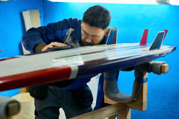 stilig man polering anpassade surfing board - surf garage bildbanksfoton och bilder