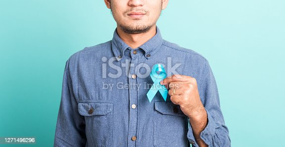 Asian portrait happy handsome man posing he holding light blue ribbon for supporting people living and illness, studio shot isolated on blue background, Prostate Cancer Awareness in November concept