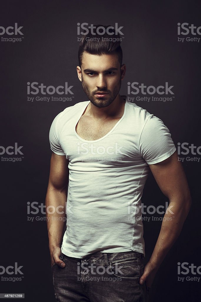 Handsome man posing in studio on dark background stock photo