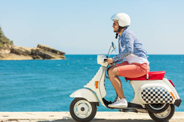 Handsome man posing on a scooter in a vacation context. Street fashion and style. stock photo