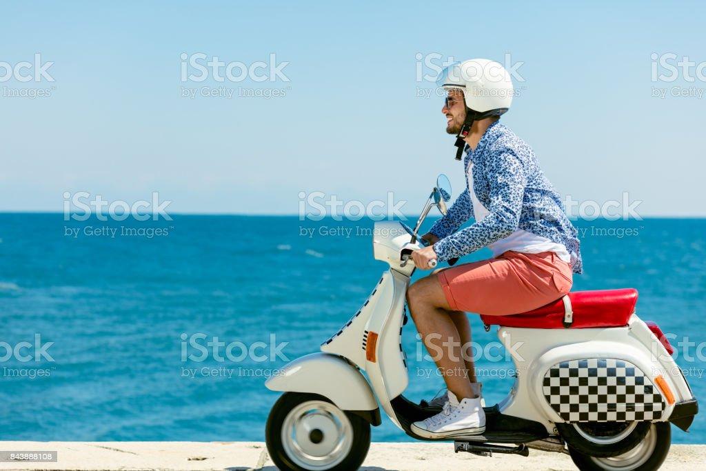 Gut aussehender Mann posiert auf einem Roller in einem Urlaub-Kontext. Street-Fashion und Style. – Foto