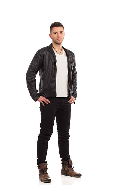 Handsome man posing Young man in black leather jacket stands with hand on hip. Full length studio shot isolated on white. leather jacket stock pictures, royalty-free photos & images