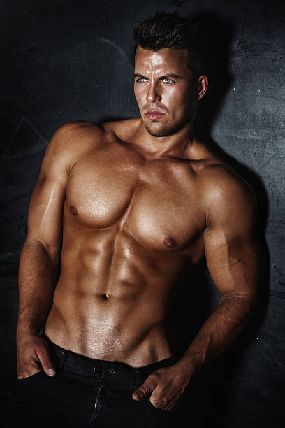 Handsome man posing Sexy fashion portrait of a hot male model with muscular body posing in studio, looking at camera. shirtless male models stock pictures, royalty-free photos & images