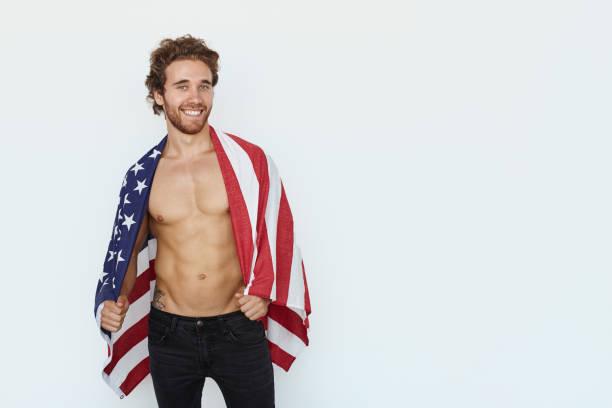 gut aussehender mann posiert mit flagge - rebellenflaggen tattoos stock-fotos und bilder