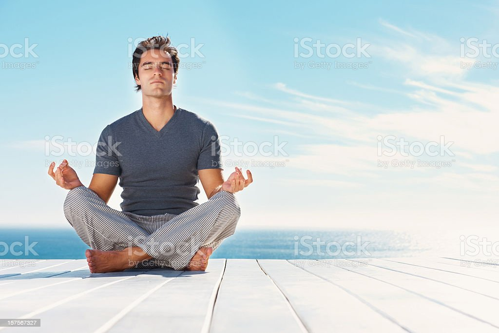 Handsome man practicing yoga outdoors stock photo