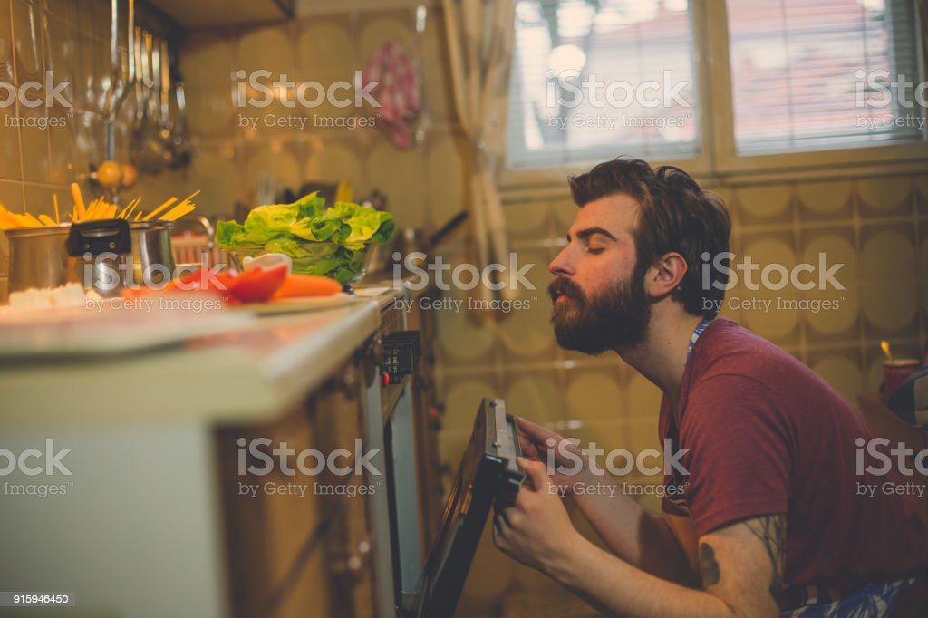 Handsome man preparing food in the kitchen at home stock photo
