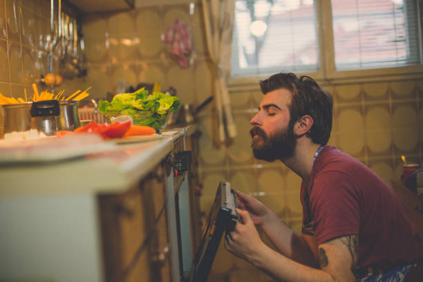 Handsome man preparing food in the kitchen at home Handsome man preparing food in the kitchen at home spaghetti straps stock pictures, royalty-free photos & images