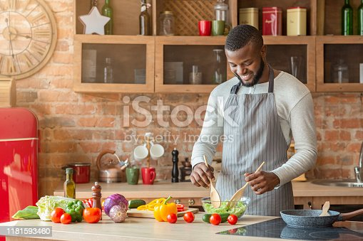 Handsome smiling black man preparing fresh healthy salad at kitchen, copy space