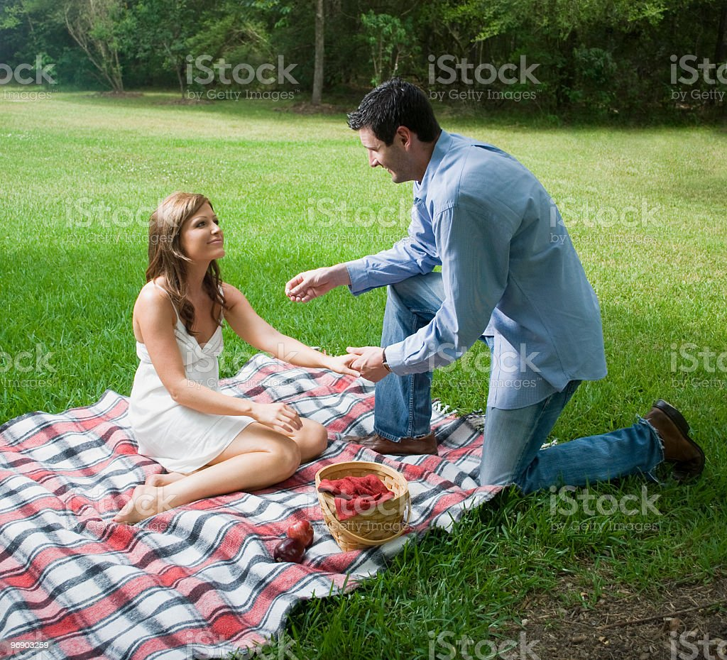 Handsome man proposing marriage to beautiful woman royalty-free stock photo