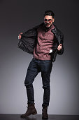 handsome man pulling his black leather jacket