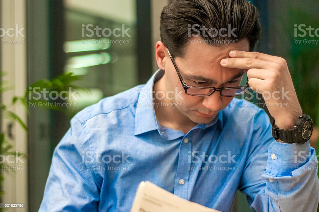 Handsome man reading a newspaper. Businessman reading a newspaper stock photo