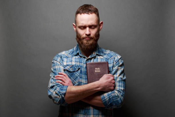 handsome man reading and praying over bible in a dark room over gray texture - preacher stock photos and pictures