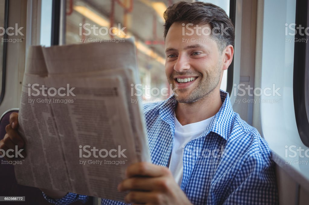Handsome man reading newspaper stock photo