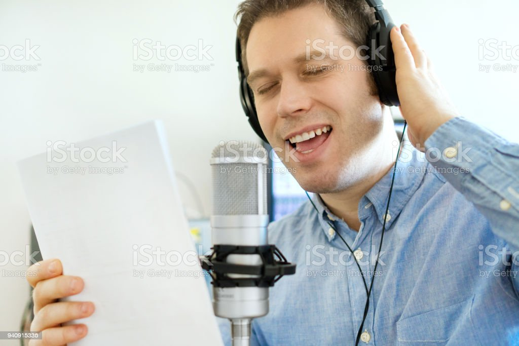 Handsome man recording a song in record studio. stock photo