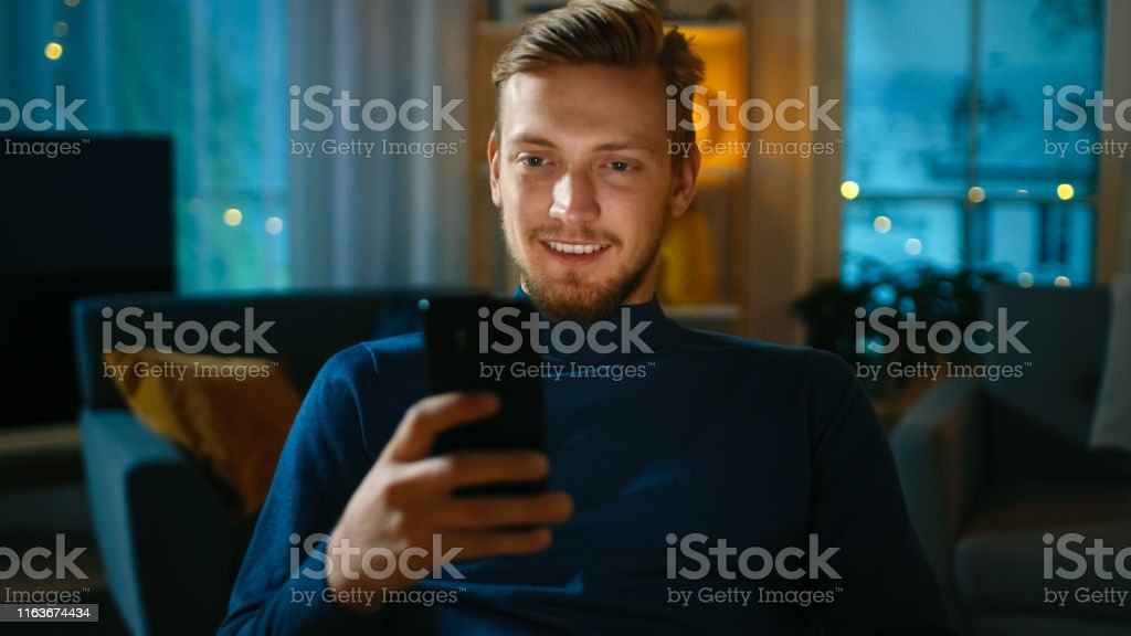 Handsome Man Relaxes at Home Uses Smartphone. In the Background Cozy...