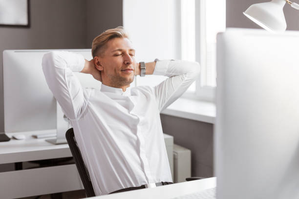 Handsome man relaxing in office Attractive adult male keeping eyes closed and leaning back on comfortable chair while working in stylish office bending over backwards stock pictures, royalty-free photos & images