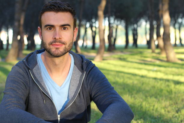Handsome man relaxing in the park stock photo