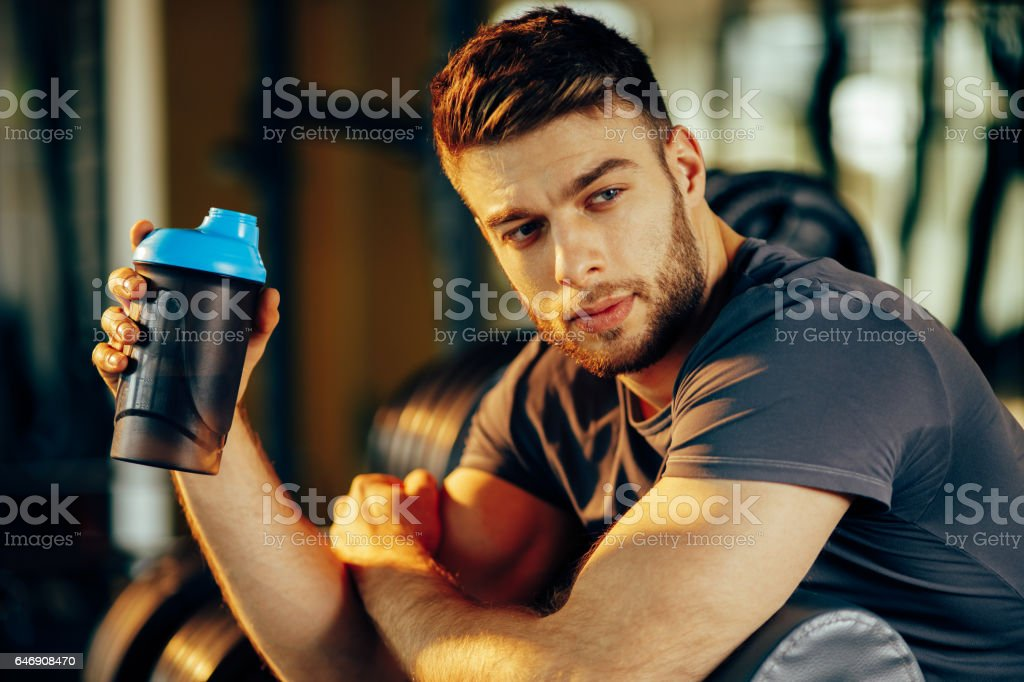Handsome man resting during a workout at the gym stock photo