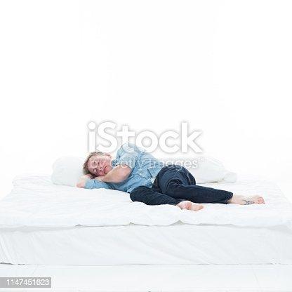 Handsome man resting on bed