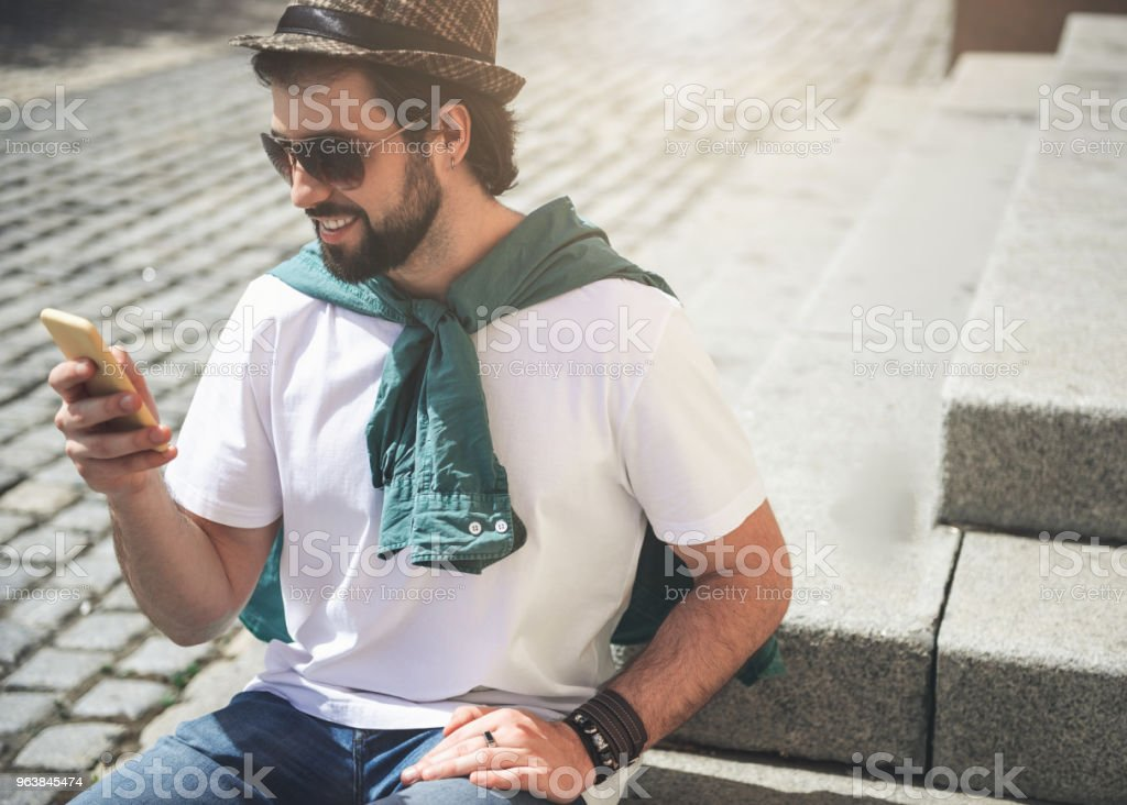Handsome man resting outside with device - Royalty-free Adult Stock Photo
