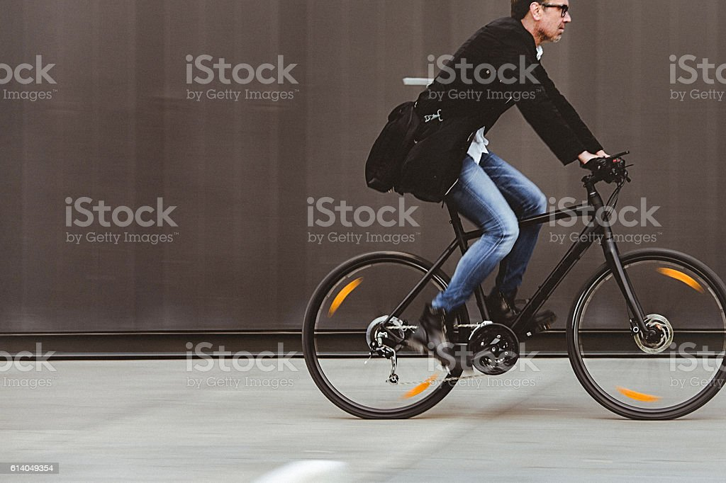 Handsome man riding bicycle beside the grey wall stock photo