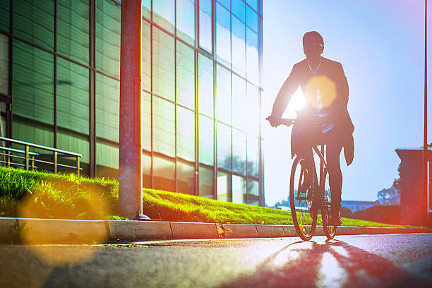 Handsome man riding bicycle beside the modern office building stock photo