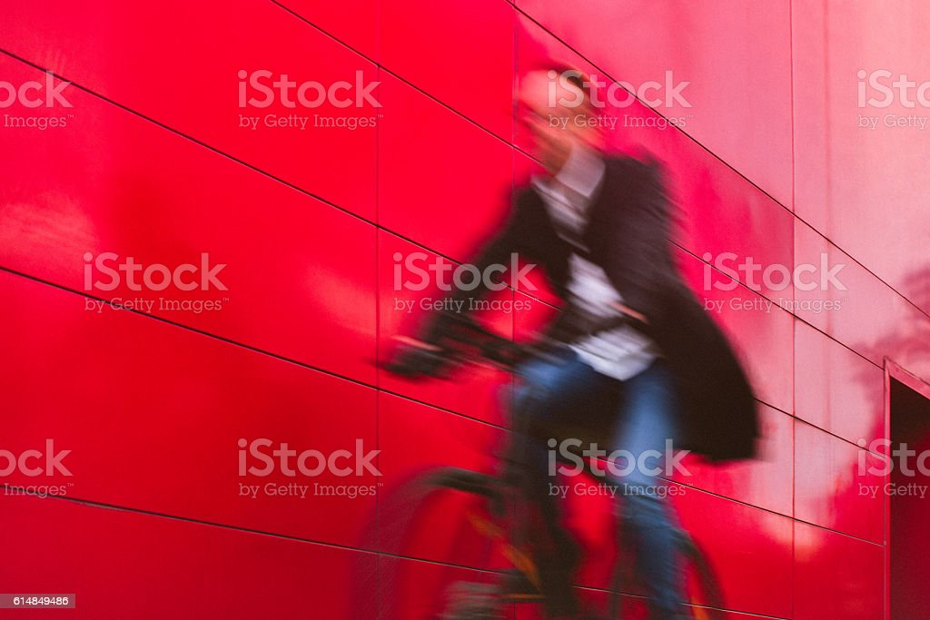 Handsome man riding bicycle beside the red wall royalty-free stock photo