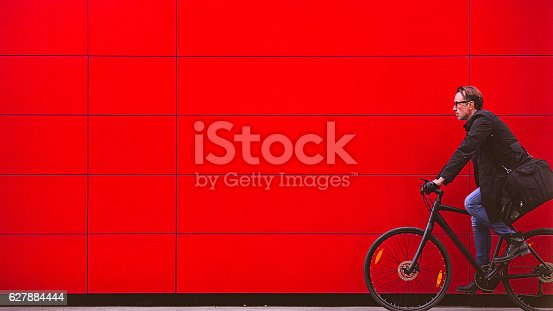 Handsome man, on the way to work, riding bicycle beside the red wall. The man is casually dressed and wears eyeglasses and carries black briefcase hung on shoulder. Motion concept, motion blur, copy space has been left.