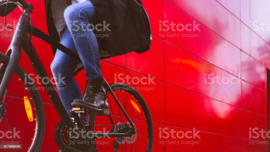 Handsome man riding bicycle beside the red wall – Foto