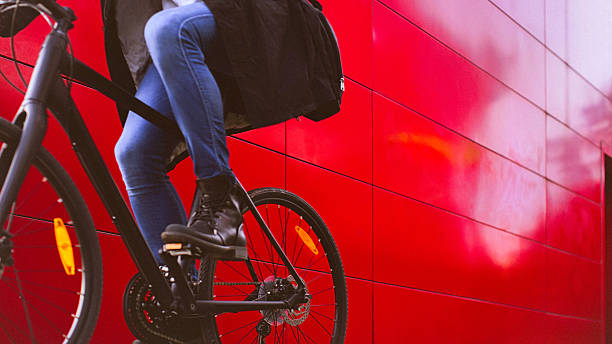 Handsome man riding bicycle beside the red wall stock photo