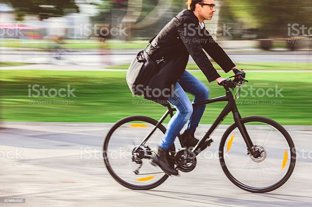 Handsome man riding bicycle on the way to work stock photo