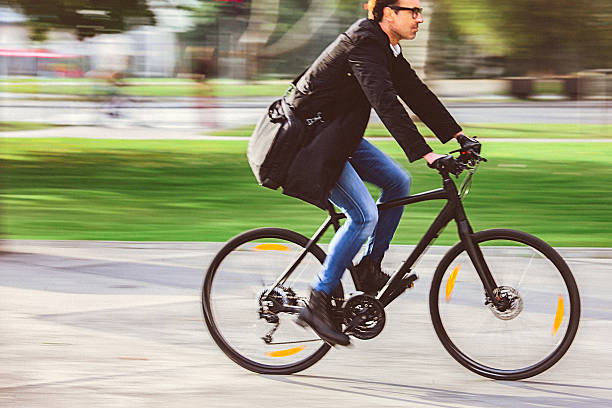handsome man riding bicycle on the way to work - écologiste rôle social photos et images de collection