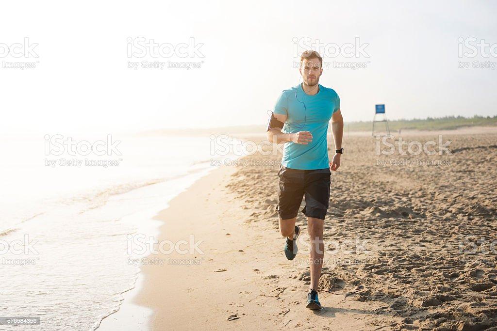 Handsome man running on the beach stock photo