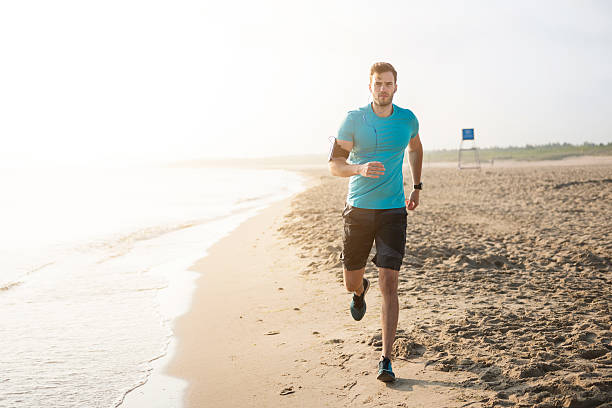 Handsome man running on the beach stock photo