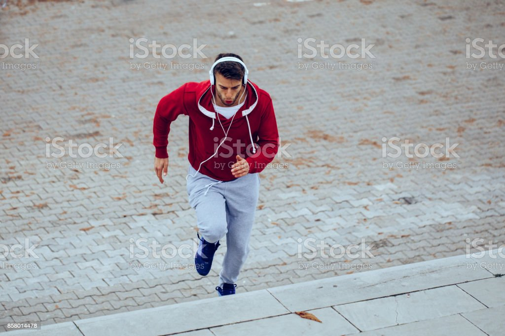 Handsome man running up at stairs stock photo
