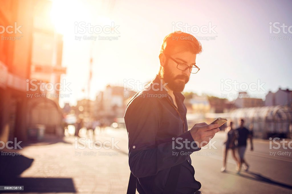 Handsome man sending text message stock photo