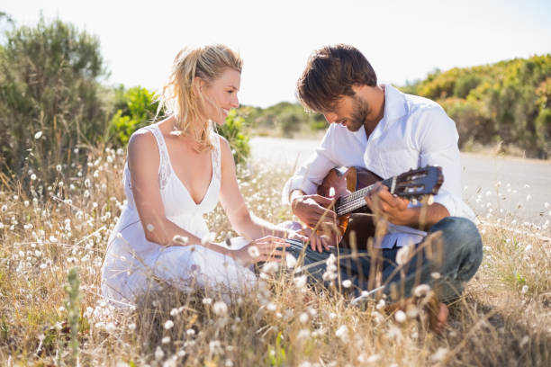 Handsome man serenading his girlfriend with guitar Handsome man serenading his girlfriend with guitar on a sunny day serenading stock pictures, royalty-free photos & images