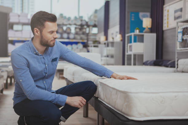 Handsome man shopping at furnishings store Young handsome man examining orthopedic mattress on sale at furniture store, copy space. Attractive male customer buying new bed at homeware supermarket. Consumerism, home concept bed furniture stock pictures, royalty-free photos & images