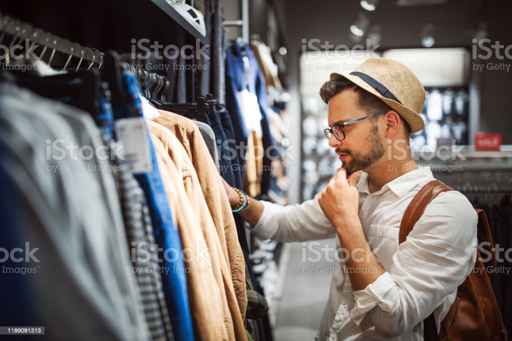 Handsome man shopping for new clothes in store Handsome young man shopping for new clothes in store Adult Stock Photo