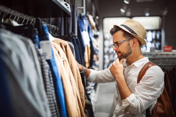 Handsome man shopping for new clothes in store Handsome young man shopping for new clothes in store menswear stock pictures, royalty-free photos & images