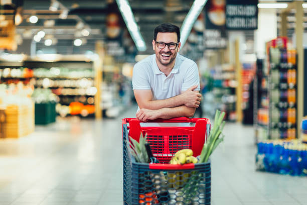 Handsome man shopping in supermarket pushing trolley and smilling. stock photo