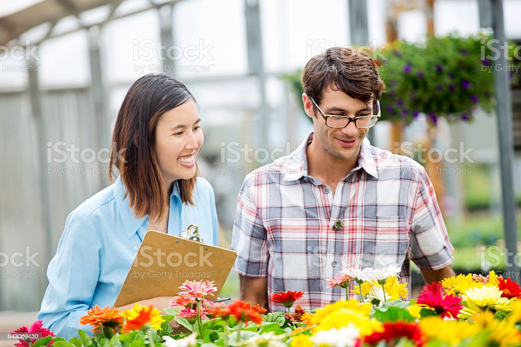 Mid adult Caucasian man shops for flowers. A young female Asian...