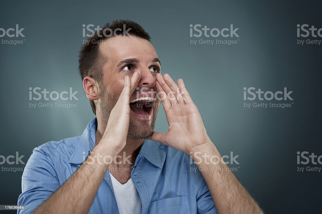 Handsome man shouting through hands royalty-free stock photo