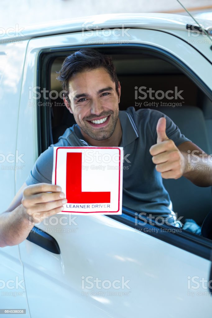 Handsome man showing thumbs up while holding L plate royalty-free stock photo