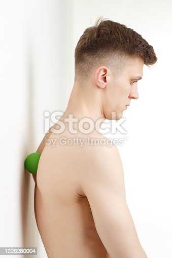 Handsome man shows exercises using wall and the mini fitness ball for a myofascial release massage of trigger points. Massage of the back spine muscle.