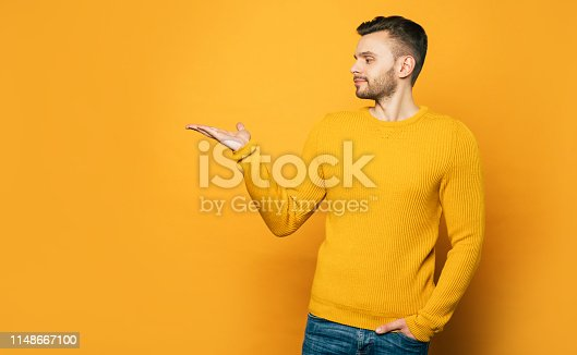 istock Handsome man shows something on his palm on copy space while standing over yellow background 1148667100