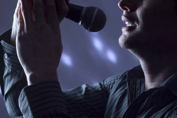 Handsome man singing to microphone with colorful background lights. stock photo