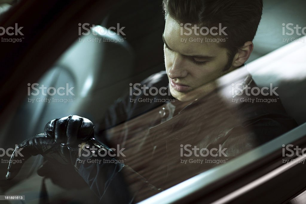 Handsome man siting in car and looking at his watch stock photo
